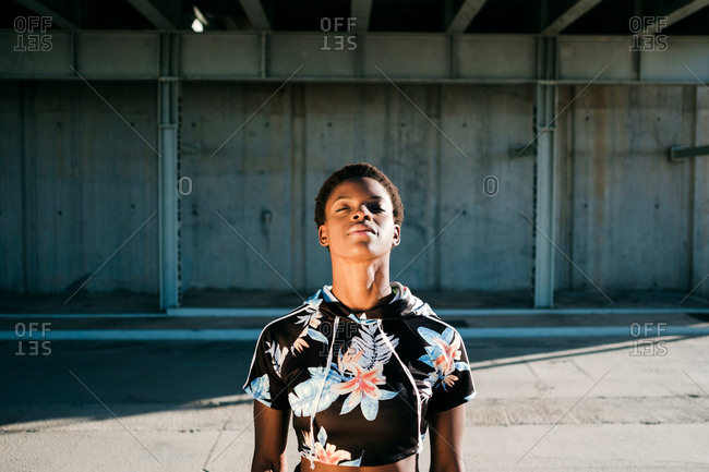 High angle of charismatic confident African American female athlete in flowered sportswear with closed eyes while standing alone on street in sunbeams against concrete wall in city
