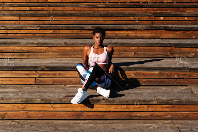 Slim African American young woman in colorful sport clothes and white sneakers looking at camera with curiosity and contemplating while sitting alone on brown wooden stairs on stadium