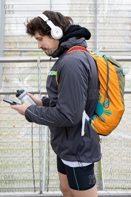 Side view of male jogger in warm jacket and shorts with backpack standing in enclosed bridge with thermos bottle and cellphone in hands and looking away