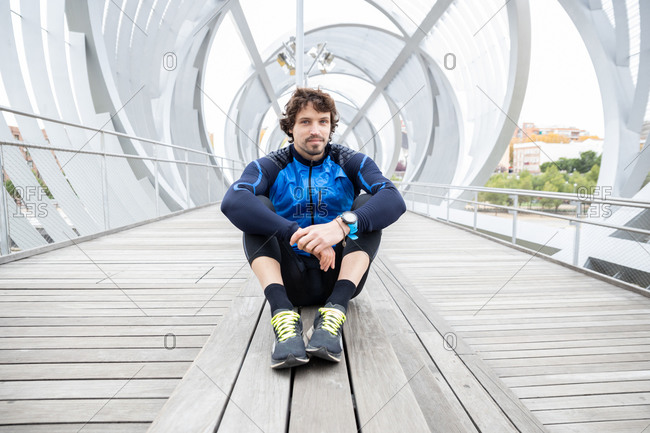 Male jogger in workout clothes sitting on wooden ground of enclosed bridge resting after workout looking at camera