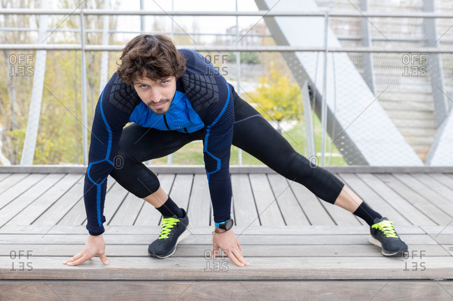 Male jogger in workout clothes sitting on wooden ground of enclosed bridge and performing leg stretching exercises