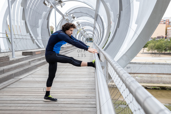 Side view of mature jogger standing on boardwalk and performing basic stretching exercises on bar at river bank at daytime