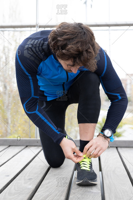 Mature male jogger in workout clothes doing up laces of sneakers during exercise on wooden boardwalk situated on river bank