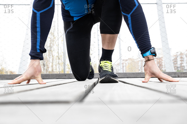 Mature male jogger in workout clothes preparing to run on wooden boardwalk situated on river bank