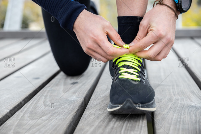 Cropped unrecognizable mature male jogger in workout clothes doing up laces of sneakers during exercise on wooden boardwalk situated on river bank