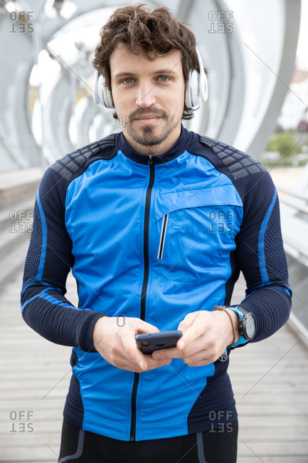 Mature bristled runner in workout clothes with headphones standing on bridge and text messaging via smartphone