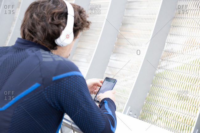 Side view of mature bristled runner in workout clothes with headphones leaning on fencing of boardwalk and text messaging via smartphone