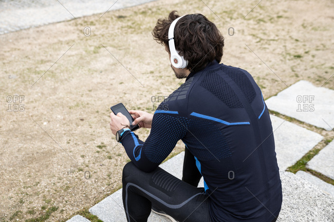 Side view of anonymous curly bristled jogger in workout clothes sitting on cobbled ground while text messaging via smartphone