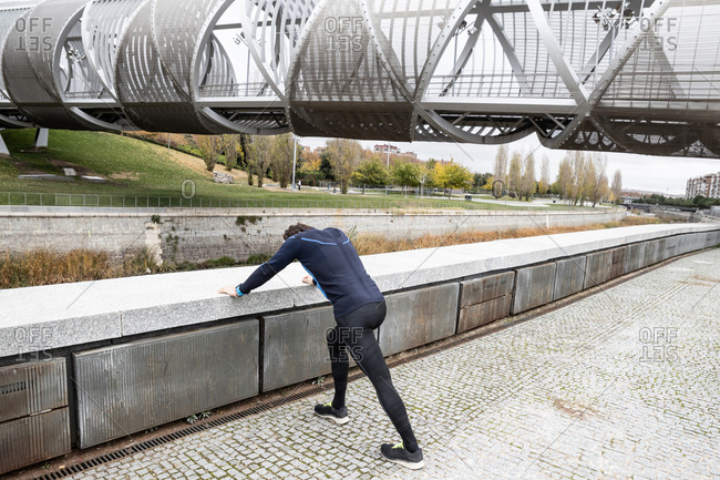 Back side view of unrecognizable jogger in leggings and tracksuit top heavily leaning on concrete fencing by river