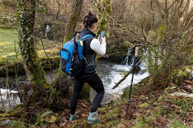Side view of faceless female trekker in active wear with backpack standing near small river in autumn forest using mobile phone to take picture