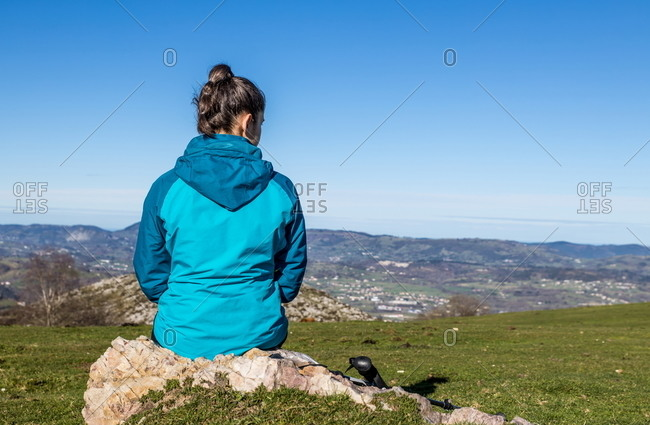Back view of unrecognizable female trekker in active wear sitting on stone on green hill with mountains and blue sky on background