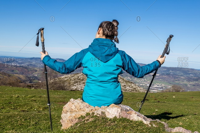 Back view of unrecognizable female trekker in active wear sitting on stone with trekking poles on green hill with mountains and blue sky on background