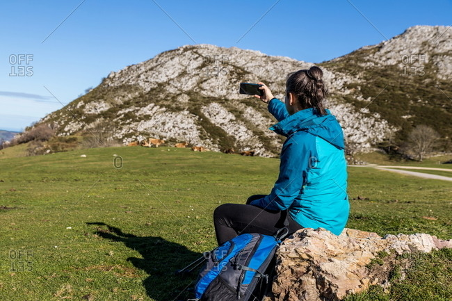 Back view of unrecognizable female tourist in active wear taking photo pf mountains on mobile phone