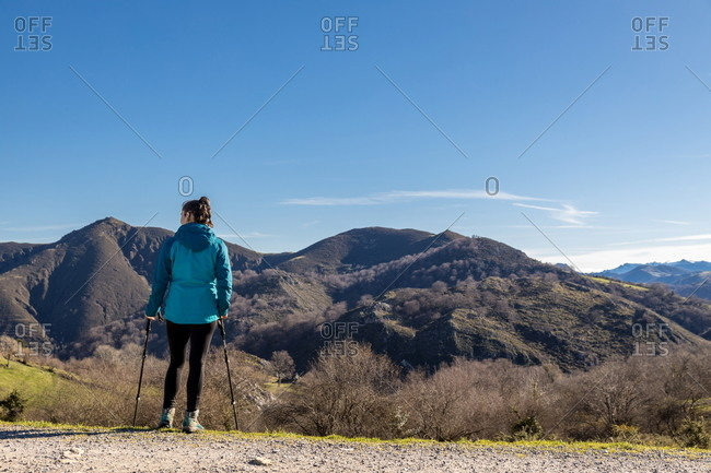 Back view of unrecognizable female trekker in active wear standing with trekking poles on green hill with mountains and blue sky on background