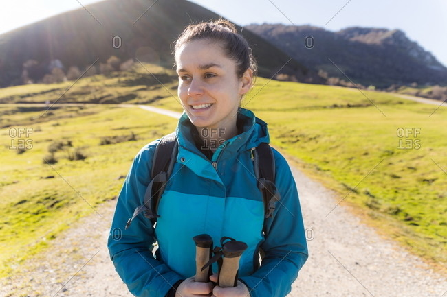 Satisfied female hiker with trekking poles smiling away with green mountains on sunny background