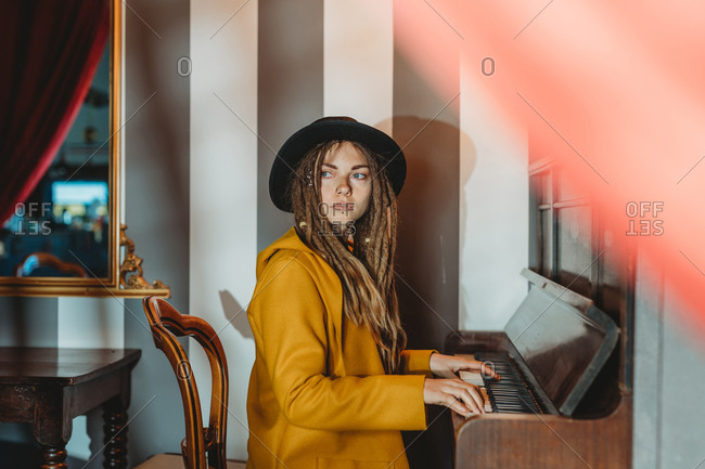 Side view of serious hipster female with dreadlocks wearing yellow coat and black hat playing piano while sitting in retro styled room