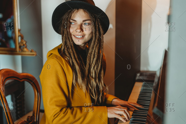 Side view of happy hipster female with dreadlocks wearing yellow coat and black hat playing piano while sitting in retro styled room