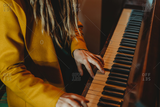Cropped unrecognizable hipster female with dreadlocks wearing yellow coat playing piano while sitting in retro styled room