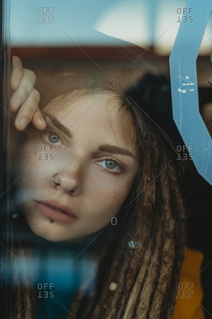 Pensive sad young female with dreadlocks leaning against window glass and looking away