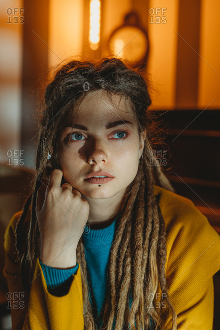 Stylish millennial female with dreadlocks wearing yellow coat over blue sweater looking away thoughtfully while sitting in room with piano in background