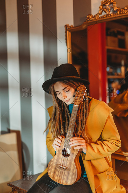 Young stylish woman with dreadlocks wearing yellow coat and black hat sitting on old wooden table back to mirror and playing Hawaiian guitar ukulele in room with antique furniture