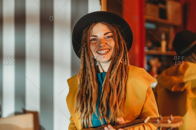 Young stylish cheerful woman with dreadlocks wearing yellow coat and black hat sitting on old wooden table back to mirror and playing Hawaiian guitar ukulele in room with antique furniture