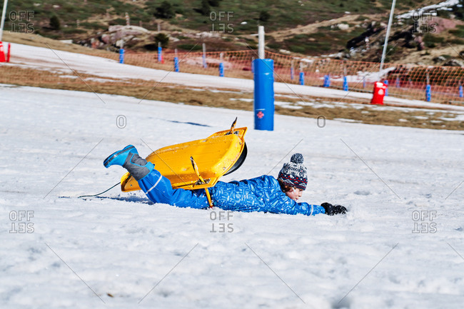 Curly boy wearing warm sportswear and knitted hat warm clothing falling off bright yellow sled on snow in mountains in Candanchu, Huesca, Spain