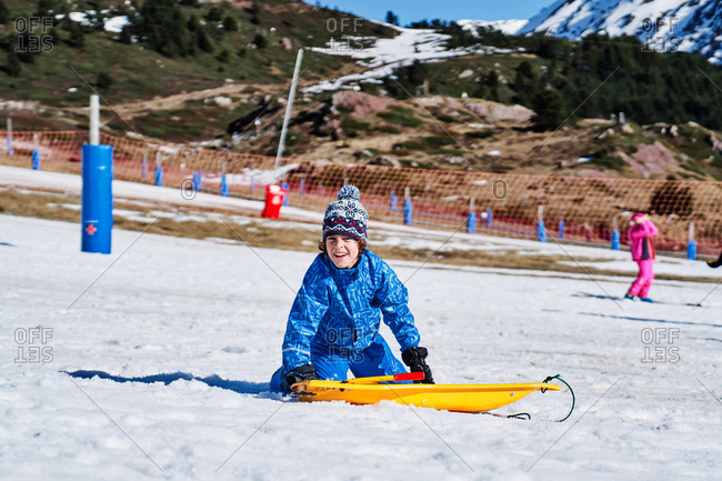 Little child wearing snowboard goggles and winter sport clothes holding onto and riding on sledge in snowy mountains in Candanchu, Huesca, Spain