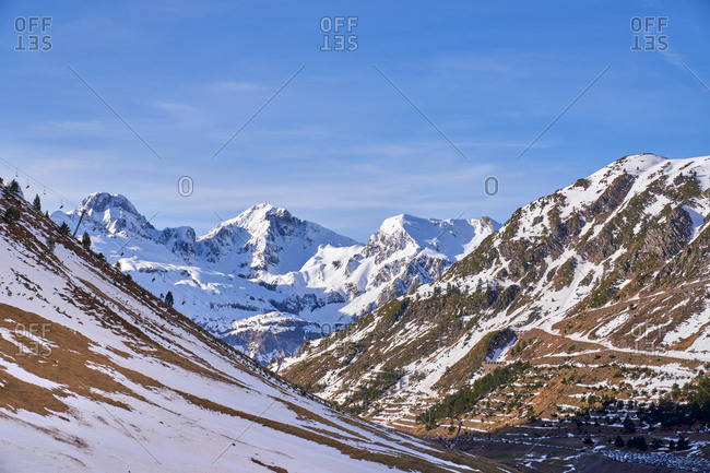 Landscape of mountains with different amount of snow and trees under cloudless blue sky casting long shadows on entire highland in Candanchu, Huesca, Spain