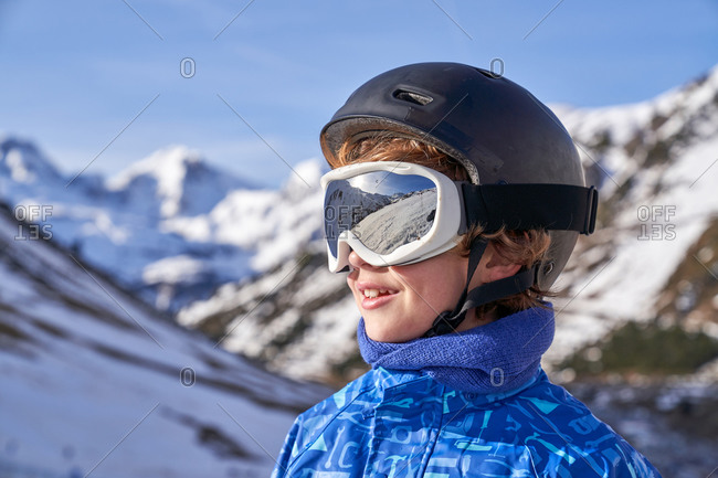 Curly boy in helmet and winter sport clothes standing on top of mountains and looking away through snowboard goggles in Candanchu, Huesca, Spain