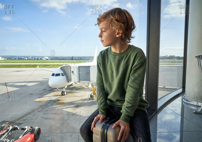 Optimistic preteen boy in casual clothes smiling and sitting on suitcase near window in contemporary airport looking away