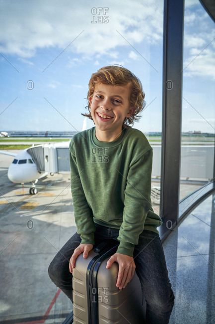 Optimistic preteen boy in casual clothes smiling and sitting on suitcase near window in contemporary airport