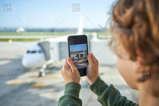 Unrecognizable kid using smartphone to take picture of modern aircraft while standing near window in airport