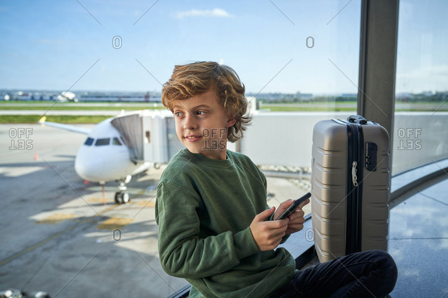 Kid using smartphone while sitting on the floor near window in airport
