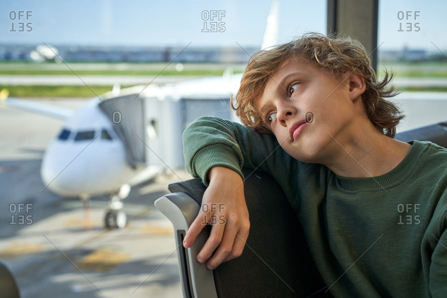 Boy relaxing on bench and looking away with dreamy glance while waiting for flight in modern airport