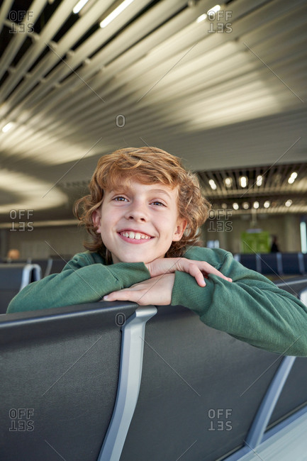Boy relaxing on bench and looking at camera with dreamy glance while waiting for flight in modern airport