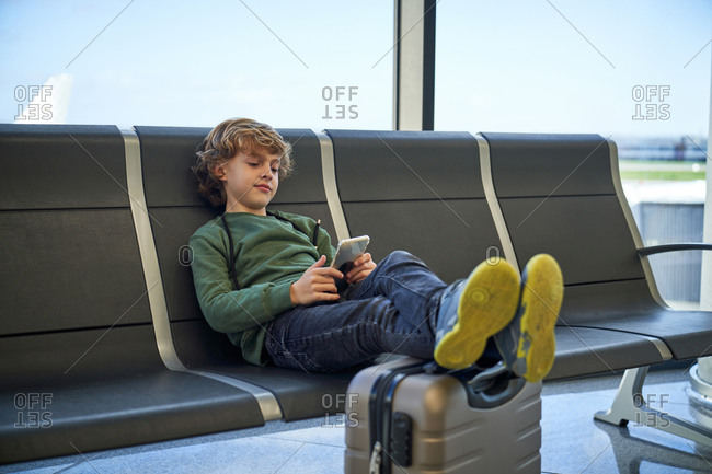 Bored boy in casual clothes sitting on bench with legs on luggage and browsing smartphone while waiting for flight in contemporary airport