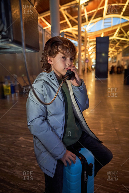 Preteen passenger sitting on luggage and speaking on telephone in evening in airport terminal looking away