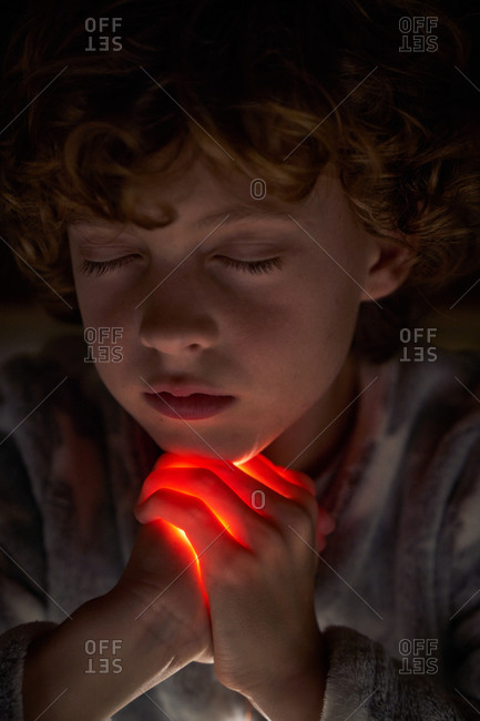 Cute child with closed eyes clasping hands with bright light and praying at night with