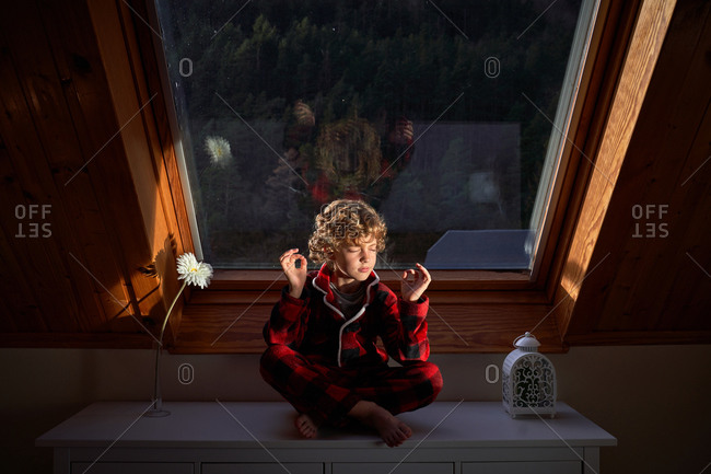 Little boy in checkered pajama sitting near window in Lotus pose and meditating with closed eyes in morning at home