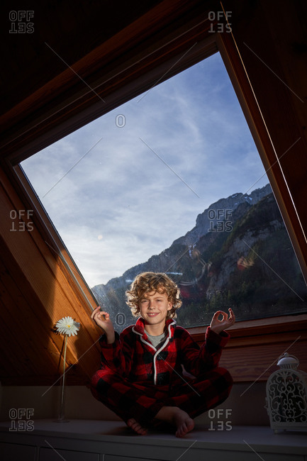 Little boy in checkered pajama sitting near window in Lotus pose and meditating while looking at camera in morning at home