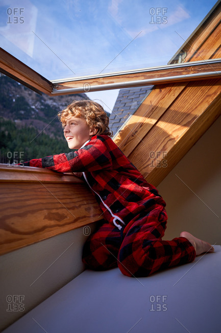 Little boy in checkered pajama looking out open window and enjoying sunny morning in weekend in suburb