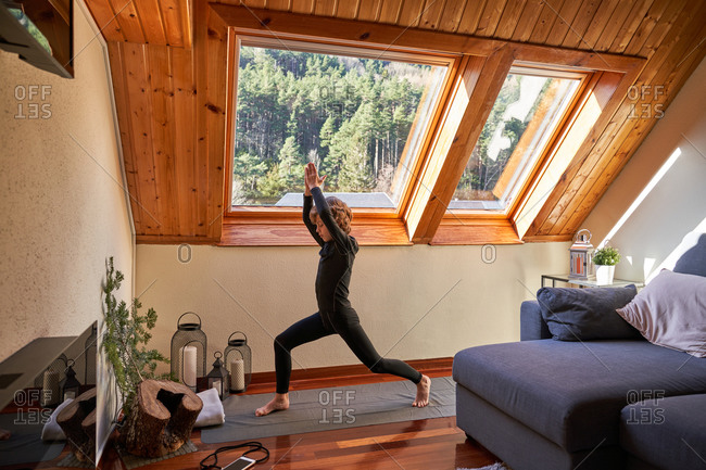 Full body little boy in black active wear standing doing yoga in the morning at home near big roof windows