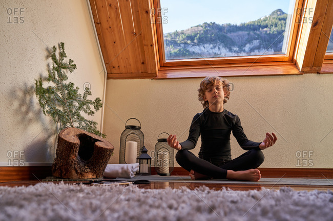 Little boy in black active wear sitting in lotus position doing yoga in the morning at home near big roof windows