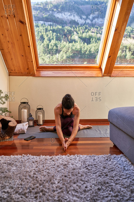Slim barefoot female with crossed legs bending forward while sitting on floor and doing yoga in morning at home