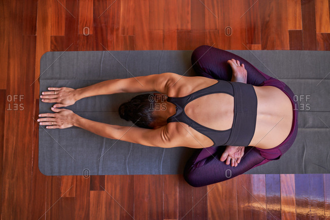 Top view slim barefoot female with crossed legs bending forward while sitting on floor and doing yoga in morning at home