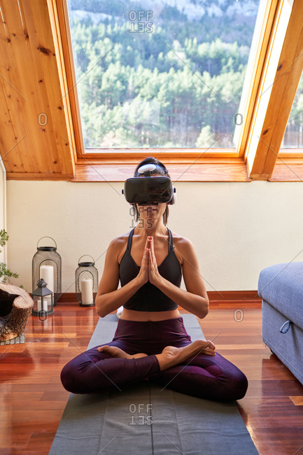 Adult female in VR glasses sitting on mat in Lotus pose and meditating while doing yoga and exploring virtual reality in morning at home
