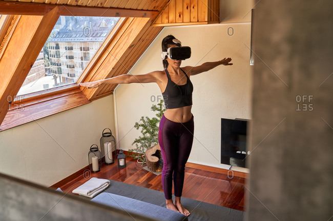 Full body barefoot lady in VR glasses standing in Mountain pose with clasped hands while doing yoga in morning at home
