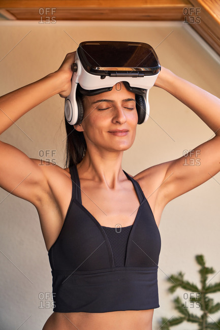 Cheerful fit woman in sportswear smiling with closed eyes and taking off VR goggles during workout at home