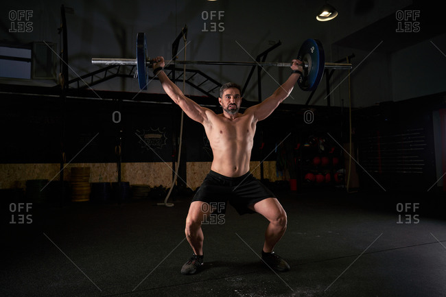 Strong man with barbell with weights in his hands doing strength exercises in the gym with magnesium in his hands. Young athlete practicing multidisciplinary training